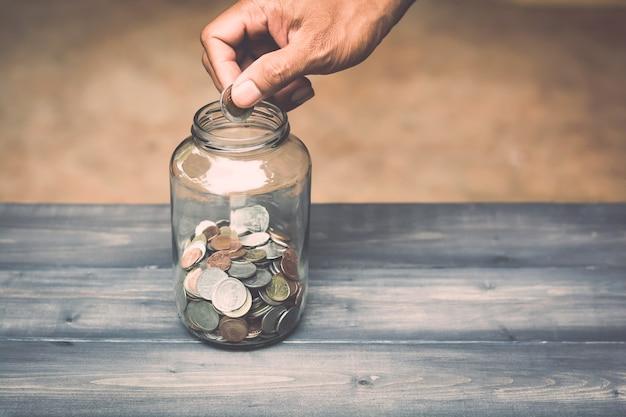 La main laisse tomber l'argent dans un pot de verre pour une économie