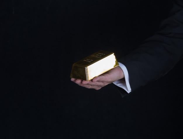 Main avec un lingot d'or sur fond noir