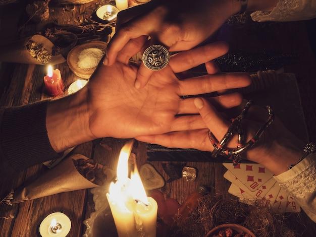 Main lisant dans le noir. bougies et attributs de l'occulte