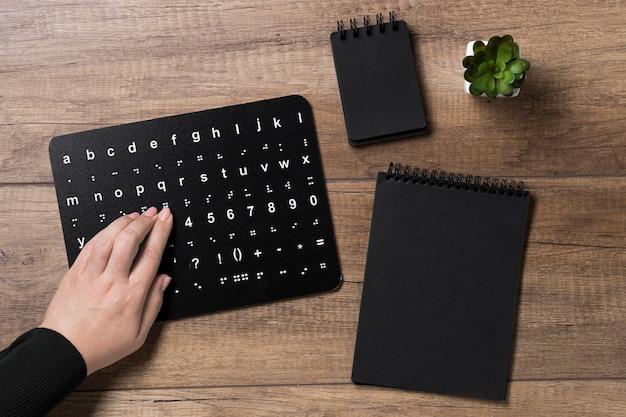 Main lisant le tableau de l'alphabet braille