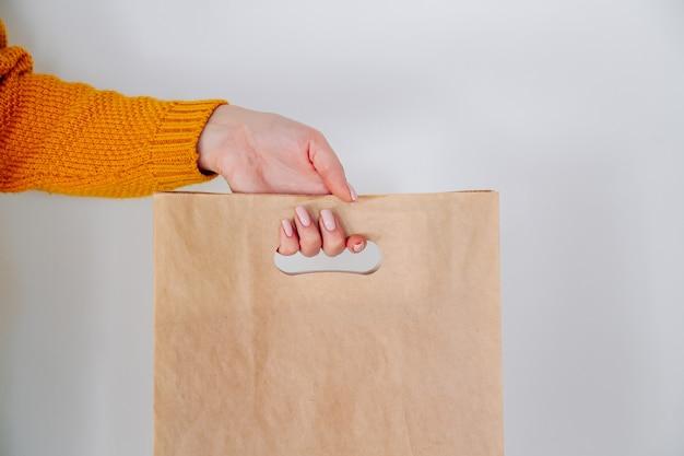 Main de livraison avec sac à provisions en papier