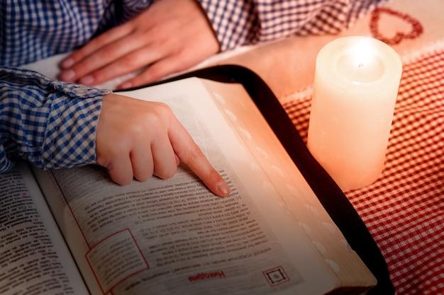 Main sur le livre à côté de la bougie. la main de l'enfant sur le livre religieux. lecture d'un livre d'évangile aux chandelles. pendant que les autres dorment.