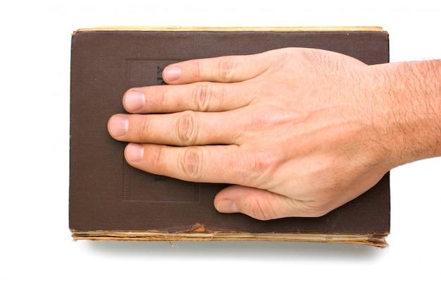 La main sur le livre isolé sur un espace blanc