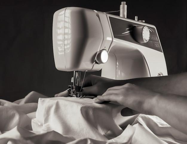 Main à la machine à coudre pendant le processus de travail avec le textile