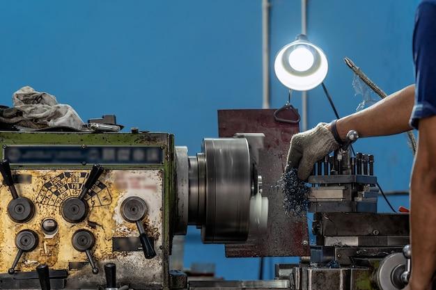 Main de machiniste professionnelle travaillant avec une machine de tours dans une usine de métallurgie