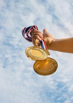 Main de la main levée et tenant deux médailles d'or