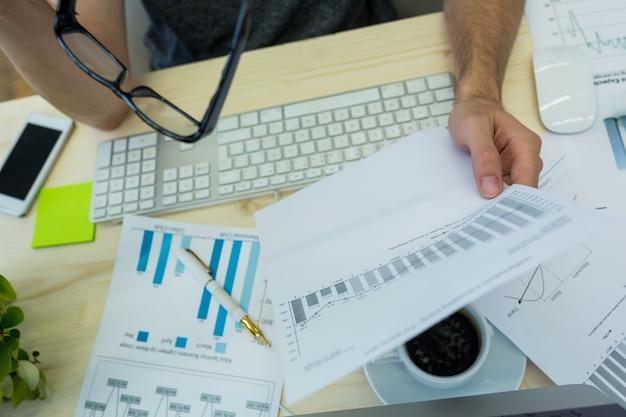 Main de mâle graphiste tenant document graphique