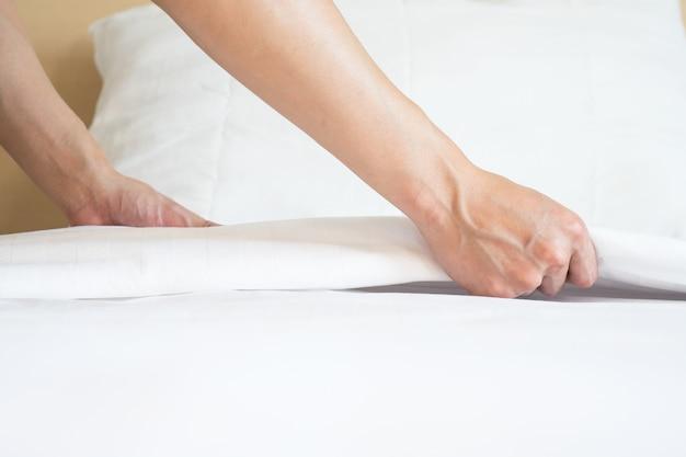 Main mâle mis en place un drap blanc dans la chambre d'hôtel