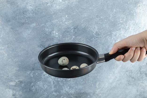 Main mâle tenant des œufs de caille bio sur une poêle à frire.