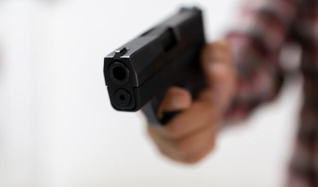 Main mâle tenant pistolet pour tirer