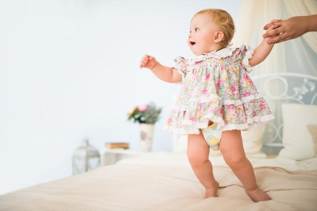 La main de mamans tient une charmante petite fille vêtue d'une robe faisant ses premiers pas sur un lit double chic contre un mur bleu et un décor