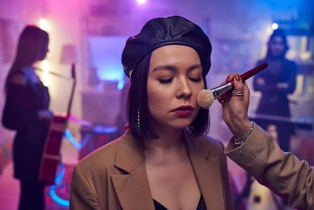 Main d'une maquilleuse appliquant de la poudre sur le visage d'une jeune femme avant d'enregistrer la performance