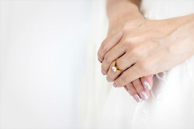 Main mariée avec belle bague en diamant sur une robe blanche.