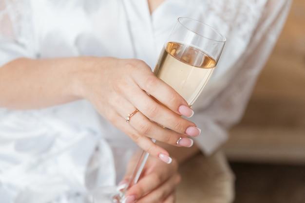 Main de mariée avec une belle manucure et une bague de fiançailles et un verre de champagne