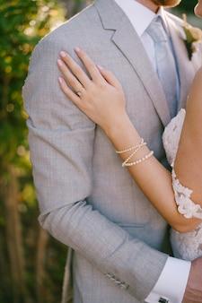 La main de la mariée se trouve sur le gros plan de l'épaule du marié