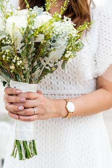 Main de mariée tenant un bouquet de fleurs pour mariage