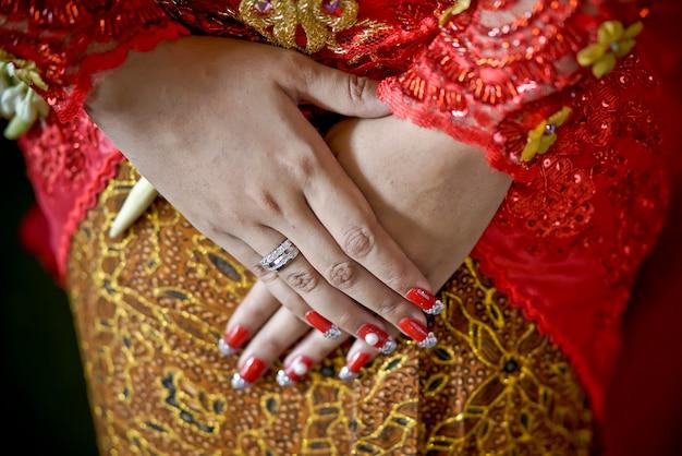 Main de la mariée traditionnelle javanaise à l'aide de kebaya et du batik de yogyakarta