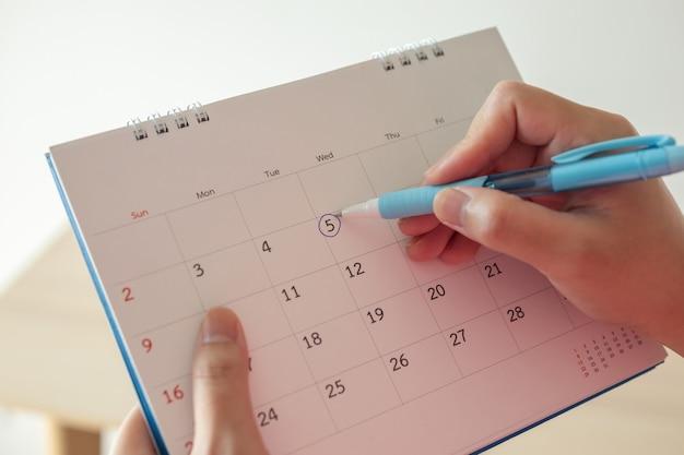 Main avec marque de stylo au 5e à la date du calendrier avec cercle bleu