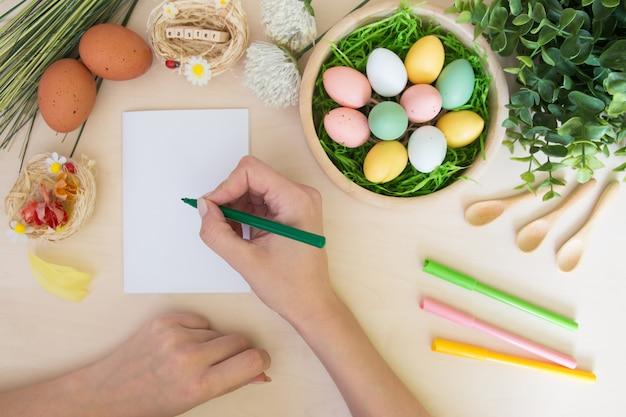 Main avec marqueur faisant des décorations de carte postale et de pâques