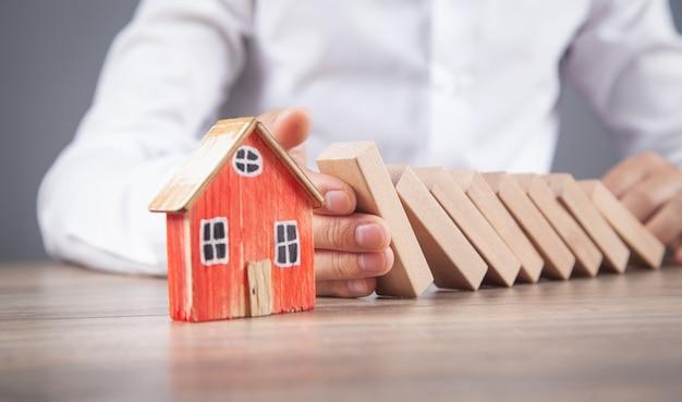 Main masculine arrêtant des blocs de bois sur la maison.