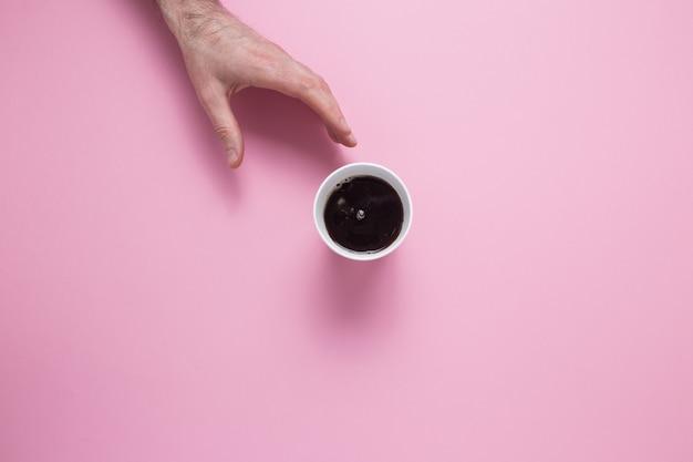 Une main masculine atteint pour un verre avec un café sur une rose