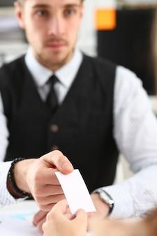 La main masculine en costume donne une carte de visite vierge au visiteur