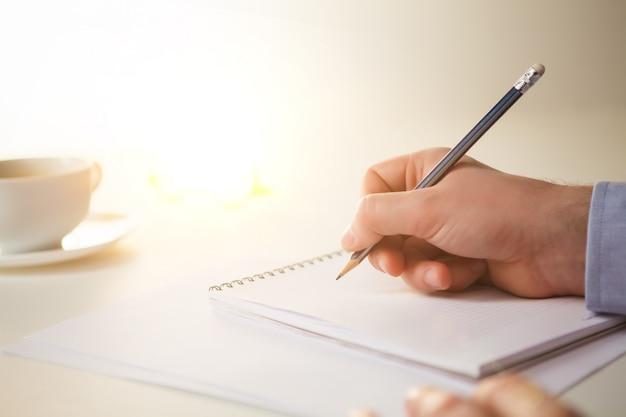 Main masculine avec un crayon et une tasse