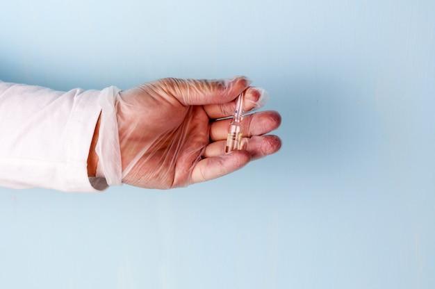 Une main masculine dans un gant médical en nitrile transparent contient un flacon de médicament.