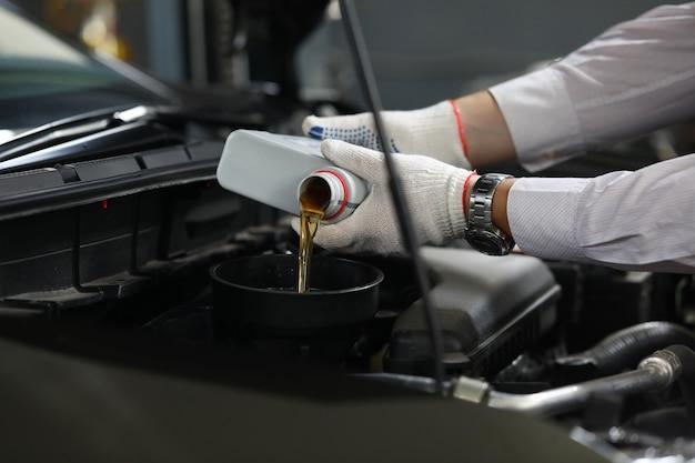 Main masculine dans des gants de protection blancs avec entonnoir