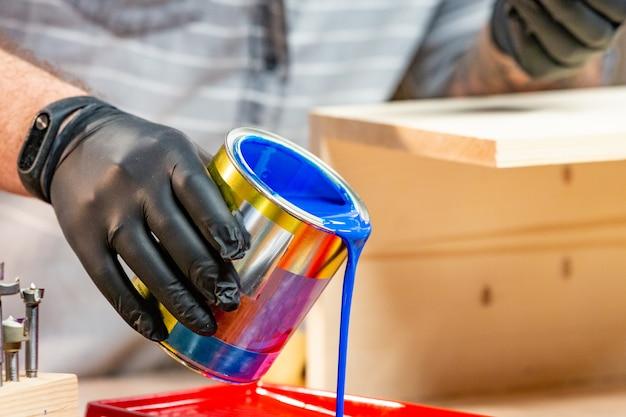 Main masculine dans des gants, verser de la peinture dans le bac, gros plan