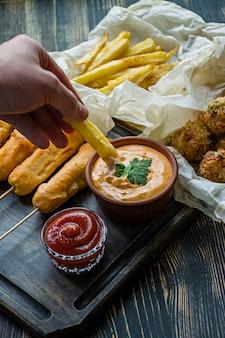 Main masculine dans une sauce pour frites.frites frites, croquettes de maïs et de chou