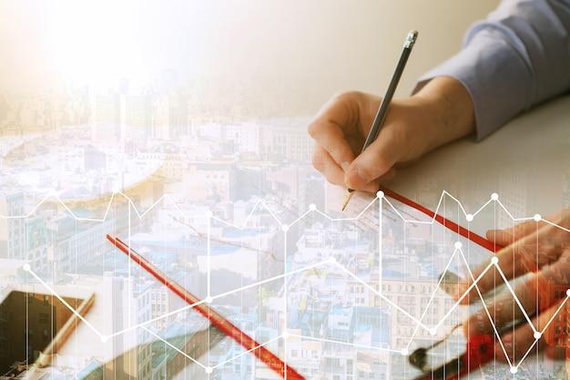 La main masculine dessinant un graphique de croissance dans le contexte de la ville abstraite