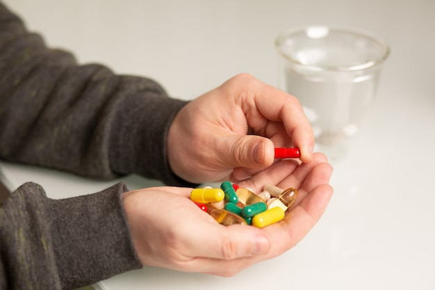 Main masculine avec diverses vitamines et suppléments pour une vie saine