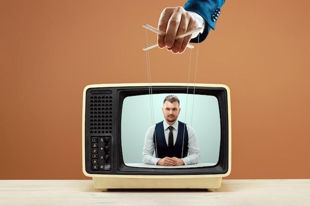 La main masculine du marionnettiste manipule l'annonceur, fake news, tromperie. le concept de gouvernement fantôme, de conspiration mondiale, de manipulation, de contrôle, de tabloïds.