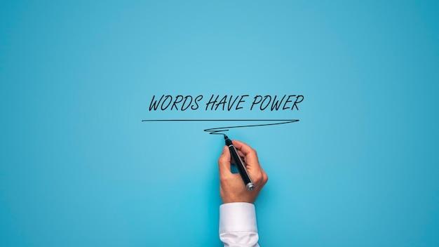 Main masculine écrivant un les mots ont un signe de pouvoir avec un marqueur noir sur fond bleu.
