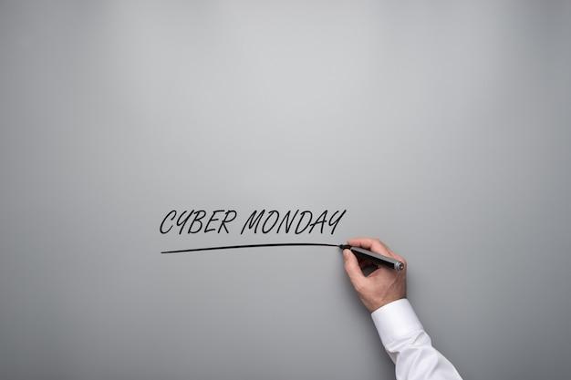 Main masculine écrivant un signe cyber monday sur un fond gris avec un marqueur noir.