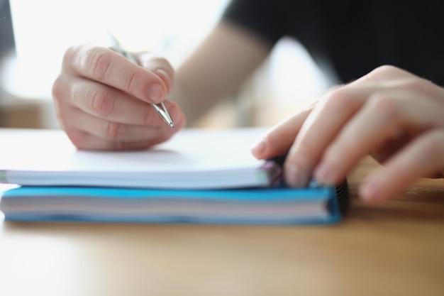 Main masculine écrivant avec un stylo à bille en gros plan pour ordinateur portable
