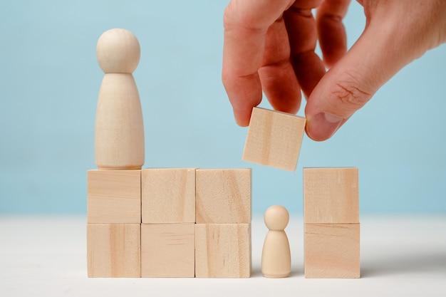 Une main masculine ferme une figure en bois par blocs sous la supervision d'une autre figure.