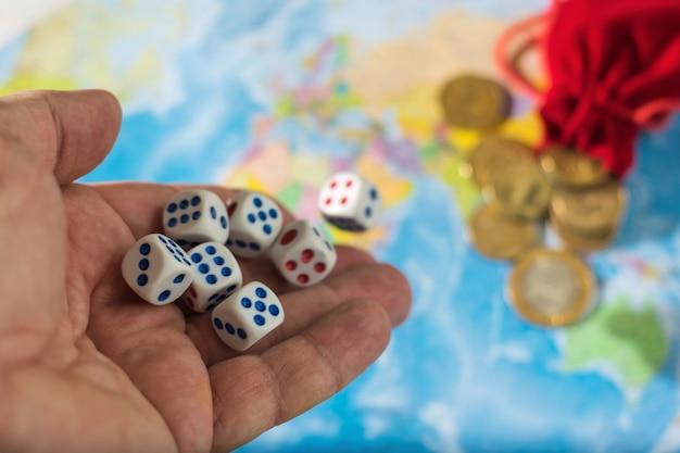 Main masculine jetant des dés sur la table avec une carte du monde et de l'argent. le concept de propriété du monde. ordre mondial.