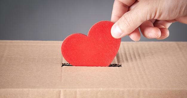 Main masculine mettant le coeur rouge dans la boîte.