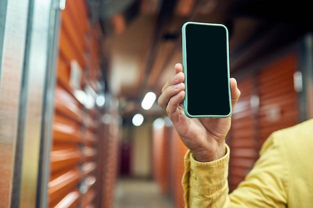 Main masculine montrant l'écran du smartphone
