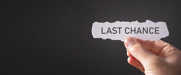 Main masculine montrant le message de la dernière chance sur du papier déchiré.