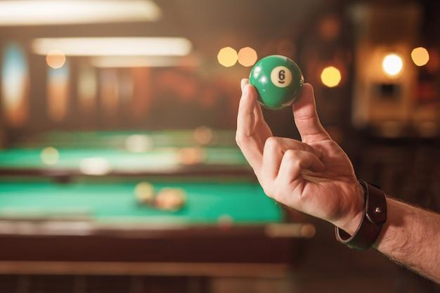 La main masculine montre une sphère de billard numéro huit.