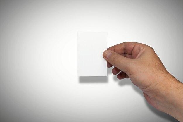 Main masculine naturellement soignée tenant une carte de visite blanche vierge. chambre pour la copie.