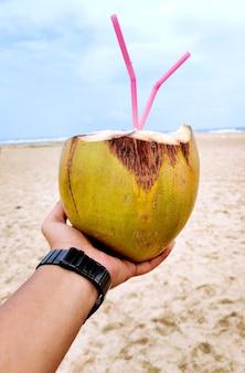 Main masculine avec une noix de coco sur la plage