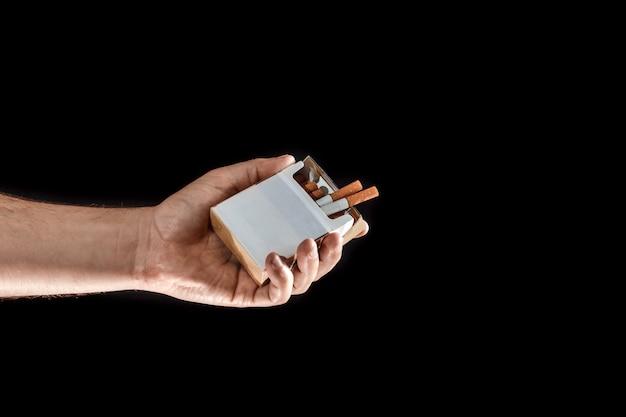 Main masculine offre une cigarette, gros plan, fond noir.
