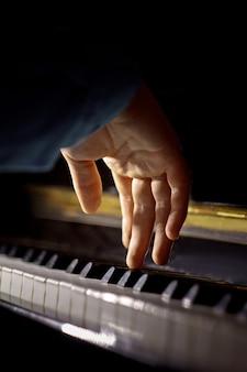Une main masculine sur le piano.