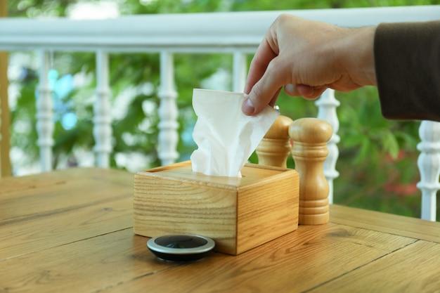 Main masculine prendre une serviette en papier dans une boîte en bois