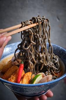 Main masculine ramassant des nouilles noires dans un bol de ramen chaud avec du bouillon de poisson, des calmars, du piment, des palourdes.