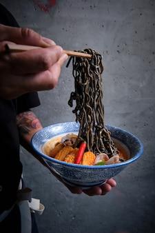 Main Masculine Ramassant Des Nouilles Noires Dans Un Bol De Ramen Chaud Avec Du Bouillon De Poisson, Des Calmars, Du Piment, Des Palourdes. Photo Premium